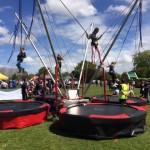 kids enjoying the 4-in-1 bungee trampoline in a fair